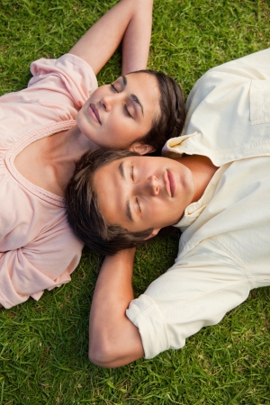 Man and a woman with their eyes closed lying head to shoulder with their arms resting behind their neck on the grass photo