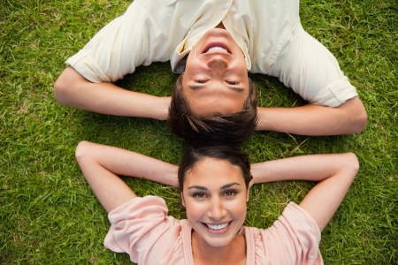 women friends: Man and a woman smiling while lying head to head with both of their arms resting behind their neck on the grass Stock Photo