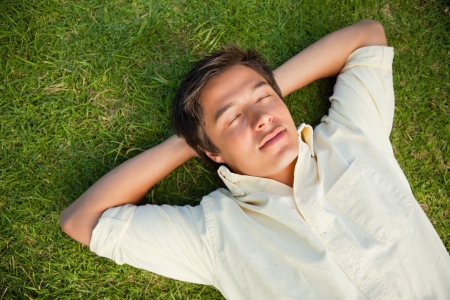 Man lying on the grass with his eyes closed and both hands resting behind his neck photo