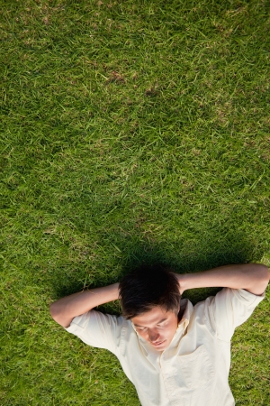 Elevated view of a man lying in grass with his eyes closed and his hands resting underneath his head photo