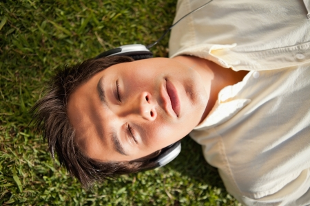 lies down: Man with his eyes closed as he uses headphones to listen to music while he lies down on the grass