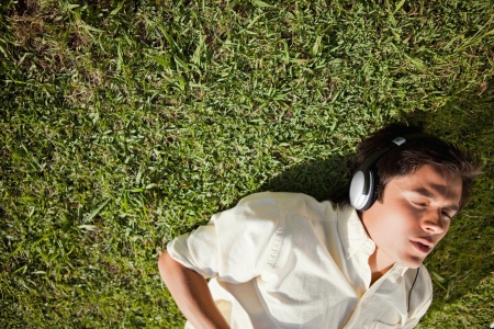 lies down: Elevated view of a man with his eyes closed while using headphones to listen to music as he lies down on the grass Stock Photo