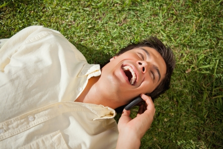 lies down: Man with his eyes closed laughing while making a call over the phone as he lies down on the grass