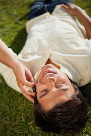 lies down: Close-up of a man with his eyes closed making a call over the phone as he lies down on the grass