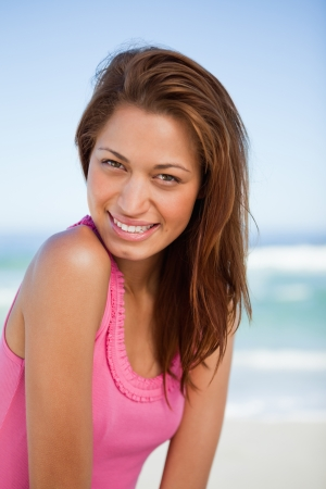 Young smiling woman standing on the beach while turning her head photo
