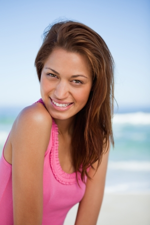 Young woman looking at the camera while standing in front of the sea and smiling photo