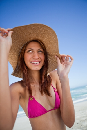 brim: Smiling attractive teenager holding her hat brim while standing on the beach Stock Photo