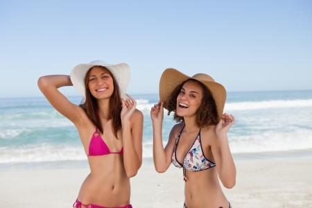 Happy young women sunbathing while standing in front of the sea side by side photo