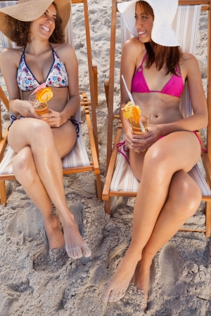 seasides: Young smiling women holding exotic cocktails while looking at each other