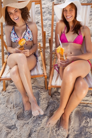 Young women laughing in deck chairs on the beach while holding fruit cocktails photo