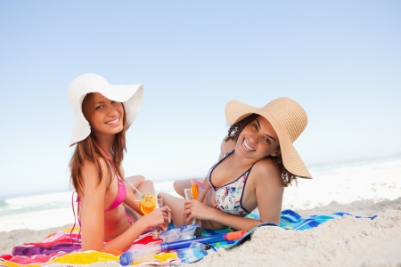 beach hat: Young women lying on beach towels while looking at the camera with smiles Stock Photo