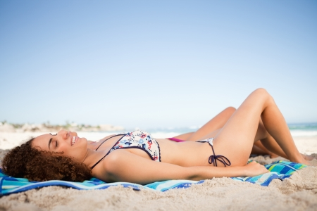 Young smiling woman lying on her beach towel and accompanied by her friend photo