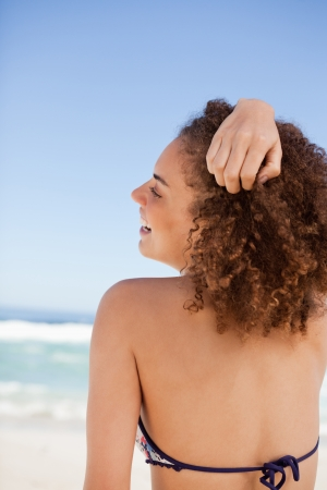 Back view of an attractive woman placing her hand on her hair in front of the sea photo