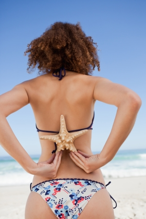 Young attractive woman in beachwear holding a starfish on her back photo