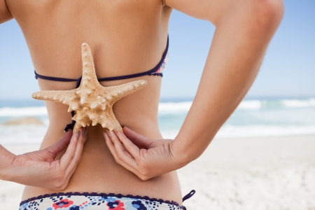 Rear view of a young beautiful woman on the beach holding a starfish on her back photo