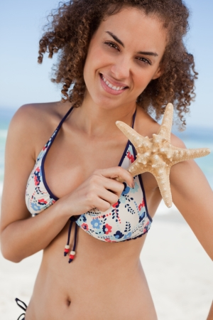 Young woman holding a beautiful starfish in front of her shoulder on the beach photo
