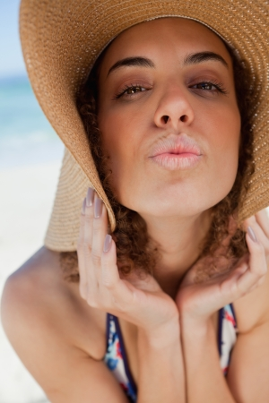 puckering lips: Young woman wearing a straw hat while puckering her lips in front of the sea
