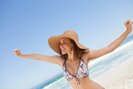 Young woman showing a great smile while opening her arms on the beach photo