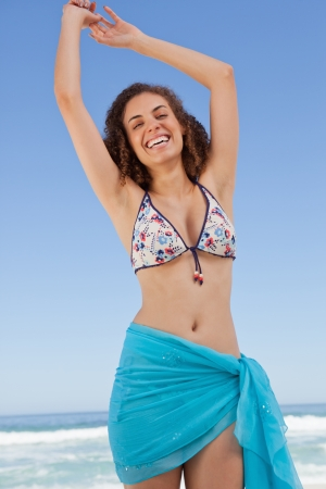 Young woman raising her arms to show her happiness while standing on the beach photo