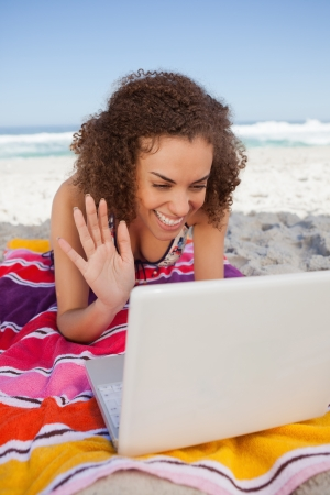 Young woman using her laptop on the beach and waving her hand in front of it photo