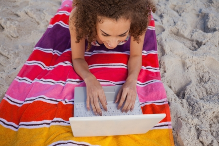 Overhead view of a young woman using her laptop while lying on the beach photo
