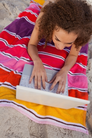Young smiling woman lying on her colourful beach towel while using her laptop photo