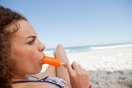 Young attractive woman eating a popsicle while lying on her beach towel photo