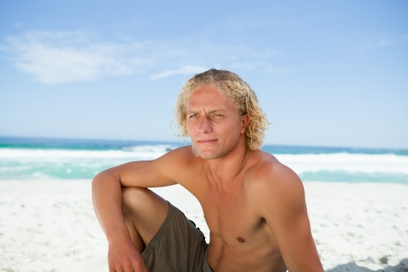 sittting: Young blonde man sitting on the beach while attentively looking towards the side