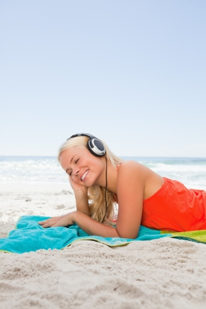 Young blonde woman lying down while listening to music with her headset photo