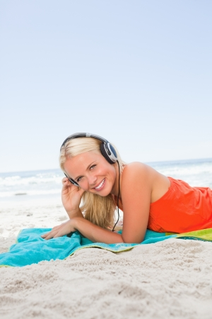 Young blonde woman lying on the beach while listening to music and smiling photo