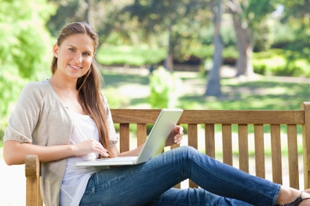 Smiling young woman with her laptop on a park bench photo
