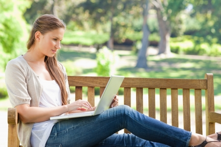 Young woman on a park bench working on her laptop photo