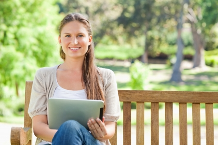 Smiling young woman with a tablet computer on a park bench photo