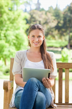 Smiling young woman on a park bench with a tablet computer photo