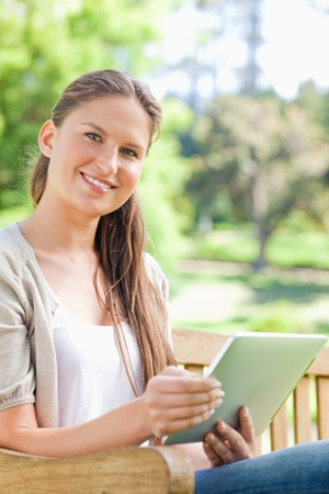 Smiling young woman with her tablet on a park bench photo