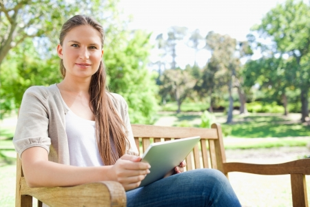 Young woman sitting on a park bench with her tablet computer photo