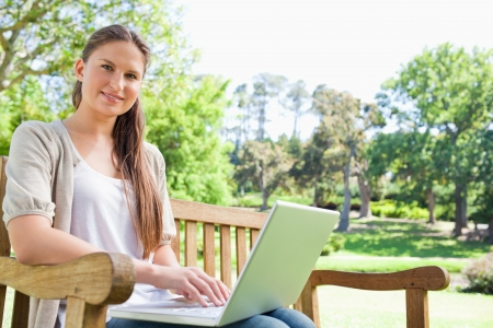 Smiling young woman with a laptop on a park bench photo