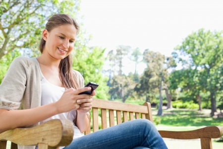 Smiling young woman reading text message on a park bench photo