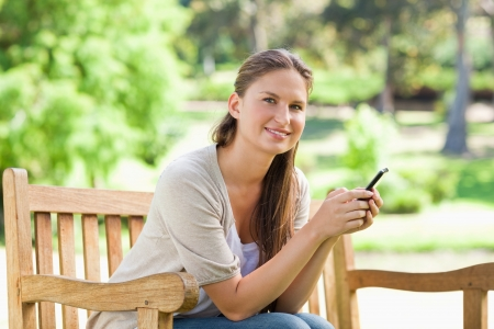 Smiling young woman sitting on a park bench with her cellphone photo