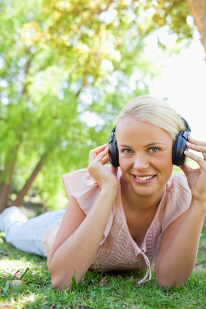 Smiling young woman with headphones enjoying music on the grass photo