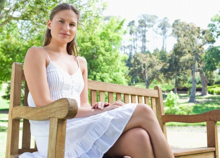 Young female sitting on a park bench Stock Photo - 13672765