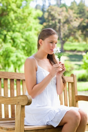 Young woman smelling on a white flower while sitting on a park bench photo