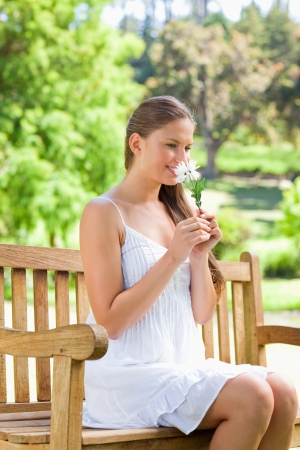 Smiling young woman smelling on a flower while sitting on a park bench photo