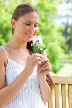 Smiling young woman on a park bench smelling on a flower photo