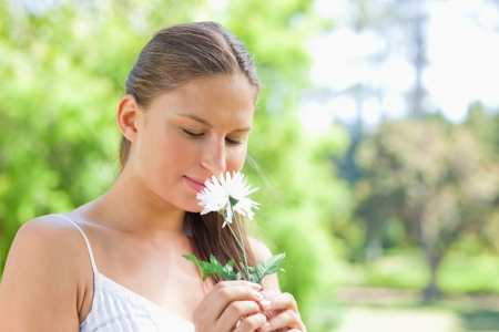 Young woman smelling on a flower in the park Stock Photo - 13672197