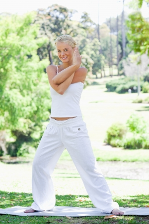 Smiling young woman doing stretches in the park Stock Photo - 13671800
