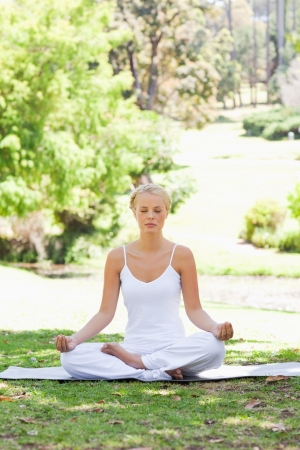 Young woman sitting in a yoga position on the grass photo