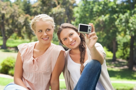 Female friends taking pictures on themselves with a camera Stock Photo - 13668235