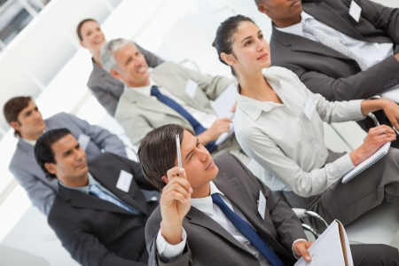 A man is asking a question at a business meeting photo
