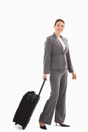 A businesswoman is walking with a suitcase photo